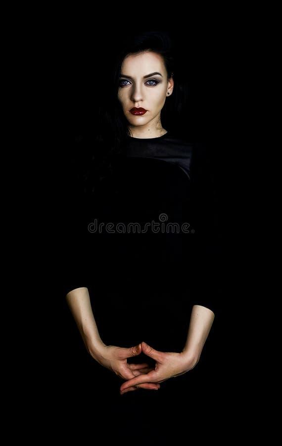 Портрет красивой женщины нося красную губную помаду и полностью черное обмундирование, черную предпосылку стоковое фото