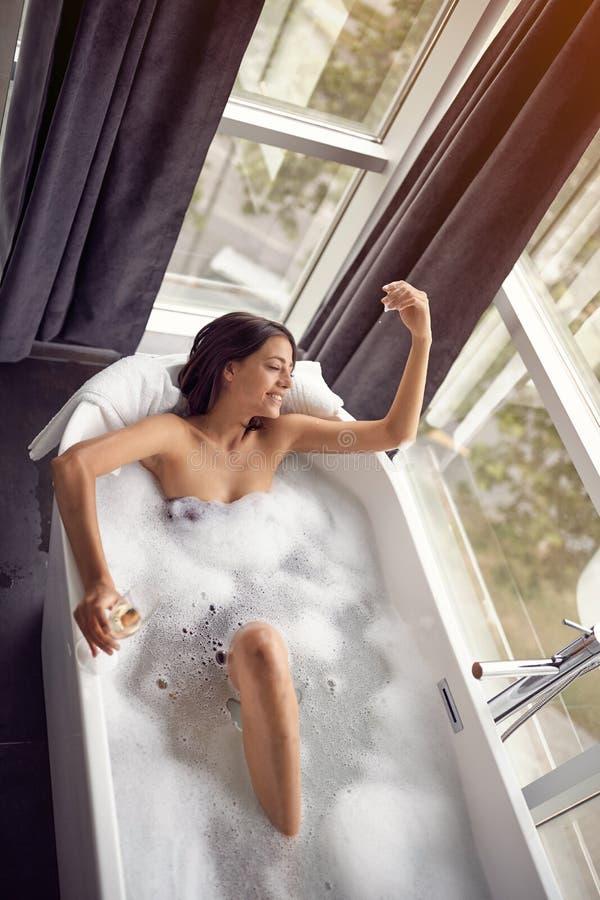 Портрет красивой женщины ослабляя в ванне с взглядом сверху пены стоковые изображения rf