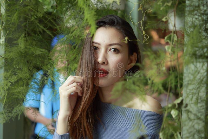 Портрет красивой женщины под смотреть листьев стоковые изображения rf