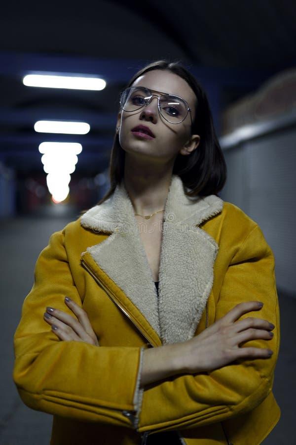 Портрет красивой женщины представляя в желтой куртке в светах города к ночь Мода улицы стоковые фотографии rf