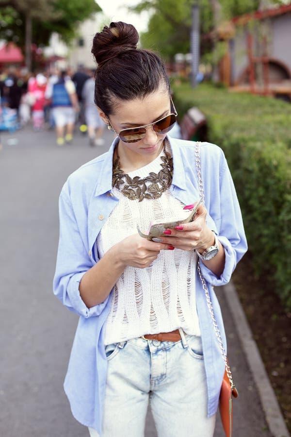 Портрет красивой женщины проверяя ее телефон стоковое изображение