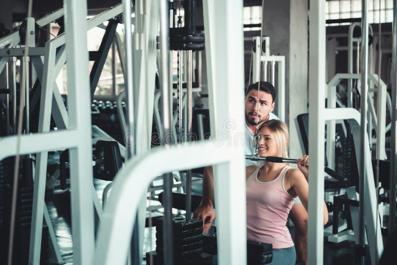 Портрет красивой женщины работает с машиной культуриста в фитнес-клубе , Привлекательный Sporty девушки делая разработку стоковые фотографии rf