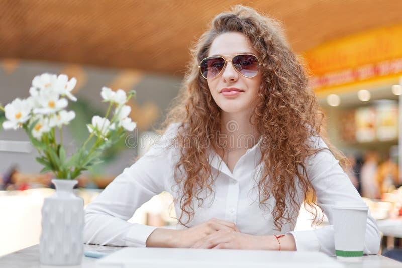 Портрет красивой женщины с вьющиеся волосы, здоровой кожей, носит ультрамодные тени, смотрит уверенно на камере, одетой в белом e стоковые изображения