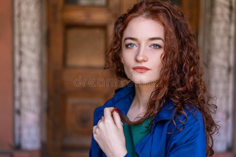 Портрет красивой женщины с красными волосами в голубом плаще представляя на камере стоковое изображение