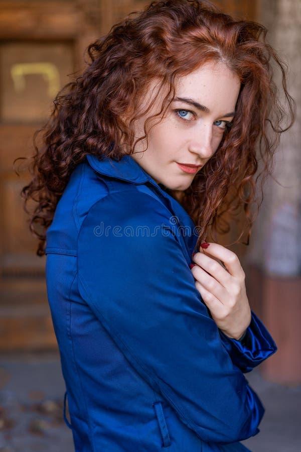 Портрет красивой женщины с красными волосами в голубом плаще представляя на камере стоковая фотография rf