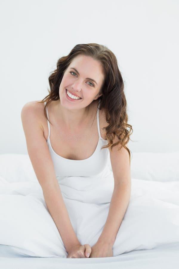 Портрет красивой женщины усмехаясь в кровати стоковая фотография