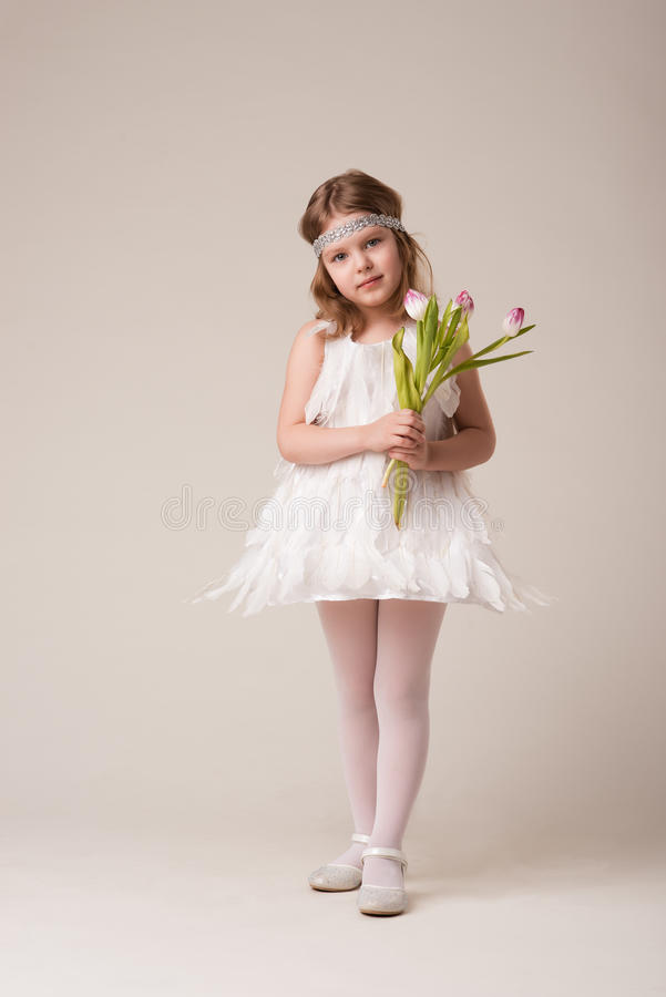 Портрет красивой жизнерадостной девушки в платье белых пер, с цветками в их руках стоковые фотографии rf