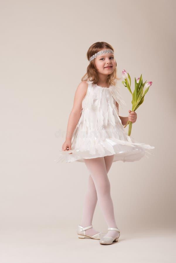 Портрет красивой жизнерадостной девушки в платье белых пер, с цветками в их руках стоковая фотография