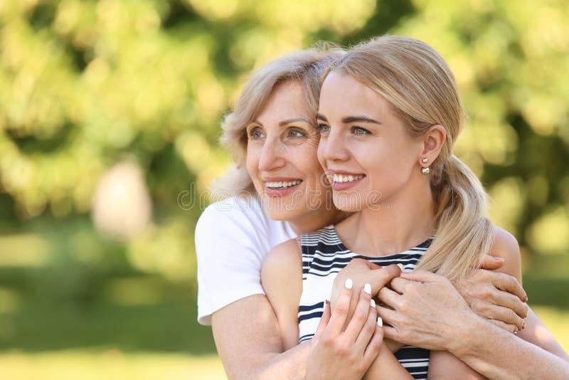 Портрет красивой зрелой женщины с ее дочерью outdoors стоковая фотография rf