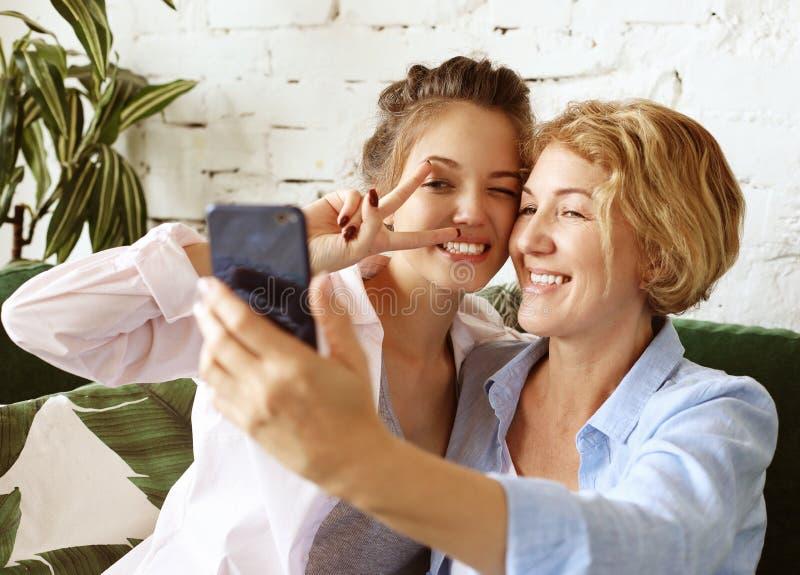 Портрет красивой зрелой матери и ее дочери, делая селфи, используя смартфон и улыбаясь, дома и счастья стоковые фотографии rf
