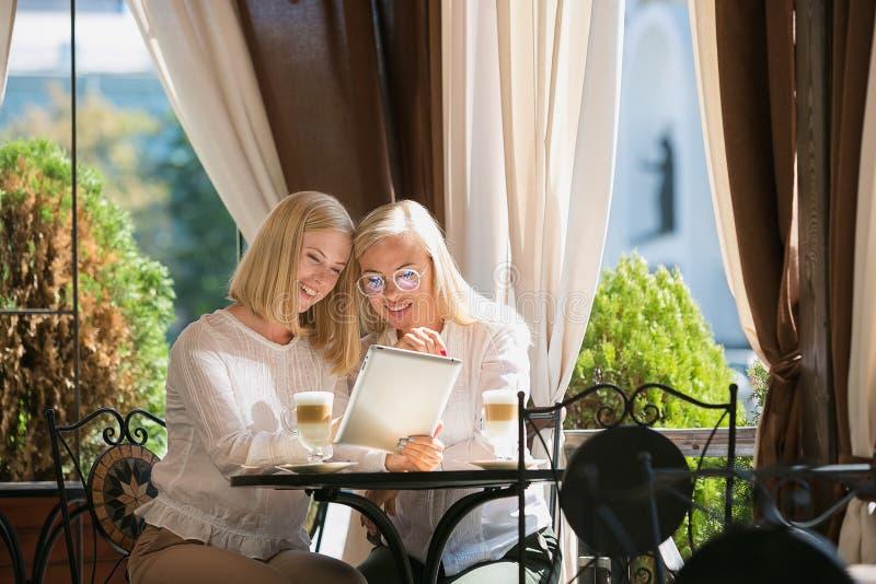 Портрет красивой зрелой матери и ее дочери держа чашку сидя дома стоковое изображение