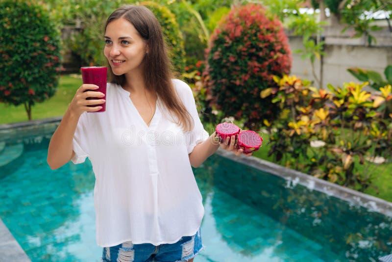 Портрет красивой маленькой девочки держа стекло smoothie плода дракона и плода в ее руках около бассейна стоковое фото rf