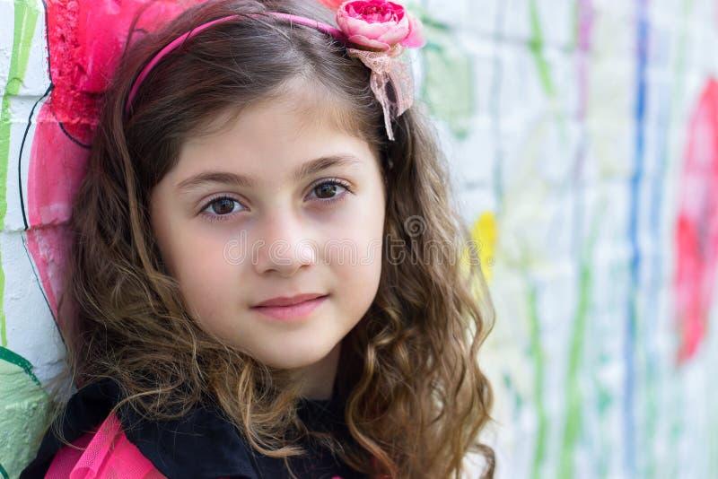Портрет красивой маленькой девочки против красочной стены стоковые изображения rf
