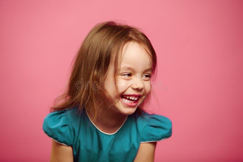 Портрет красивой маленькой девочки смеясь над счастливо на пинке изолировал предпосылку стоковые фото