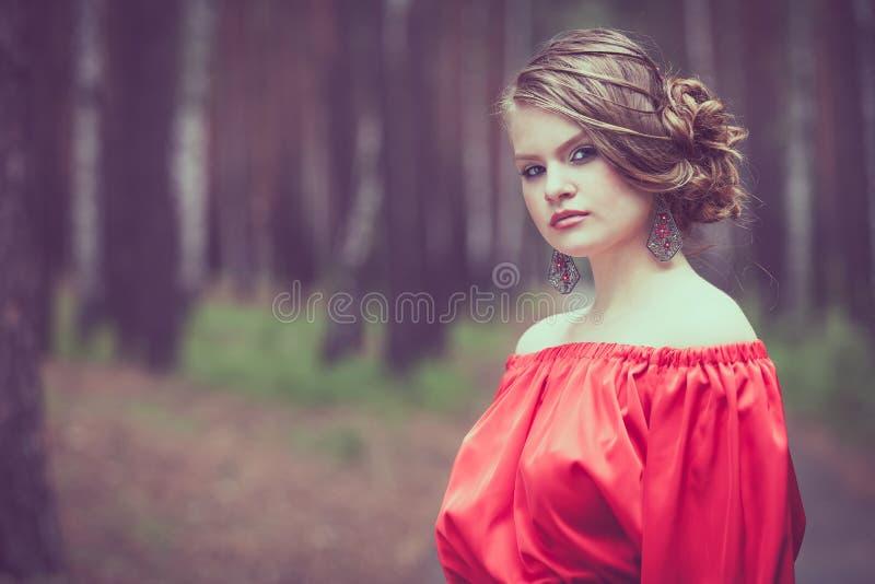 Портрет красивой маленькой девочки в красном платье outdoors стоковые фото