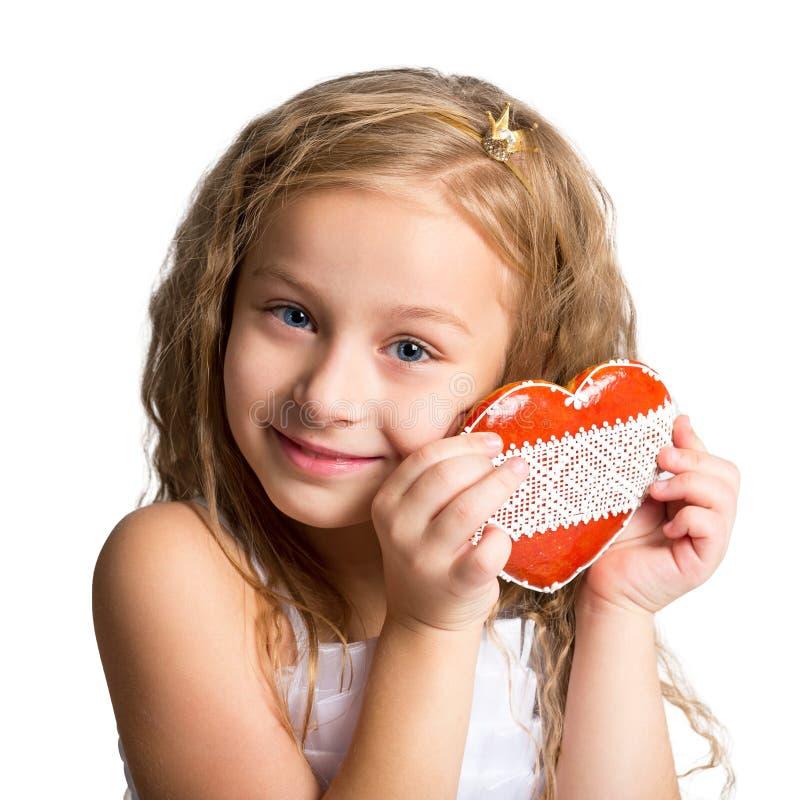 Портрет красивой маленькой девочки с пряником в форме сердц Фото ребенок на белой предпосылке стоковые фотографии rf