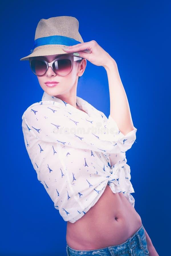 Портрет красивой модели в шляпе с стеклами, изолированный на голубой предпосылке стоковые изображения