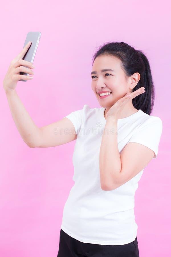 Портрет красивой молодой азиатской носки женщины белая футболка Используя умный телефон принимая selfie и усмехаться стоковое изображение