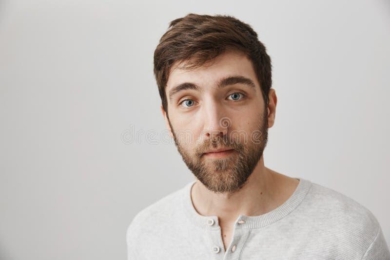 Портрет красивой молодой бородатой мужской модели с спокойным и расслабленным выражением, мельком взглядывая на камере пока стоящ стоковые изображения