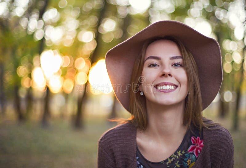 Портрет красивой молодой женщины брюнета с сияющими прямыми волосами в коричневой шляпе в парке стоковые изображения rf