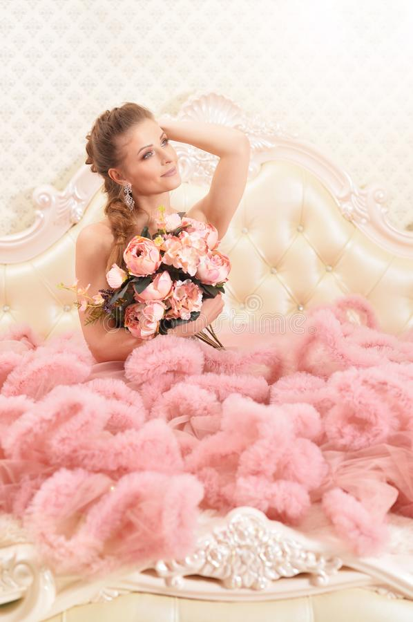 Портрет красивой молодой женщины в розовом платье представляя в спальне стоковые фото