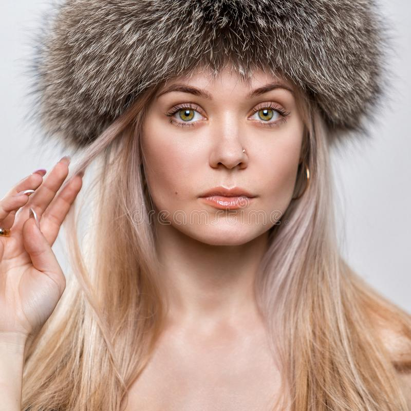 Портрет красивой молодой женщины в ультрамодной меховой шапке Женский крупный план стороны стоковые изображения rf