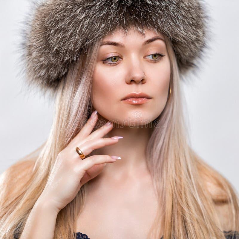 Портрет красивой молодой женщины в ультрамодной меховой шапке headdress стоковое изображение