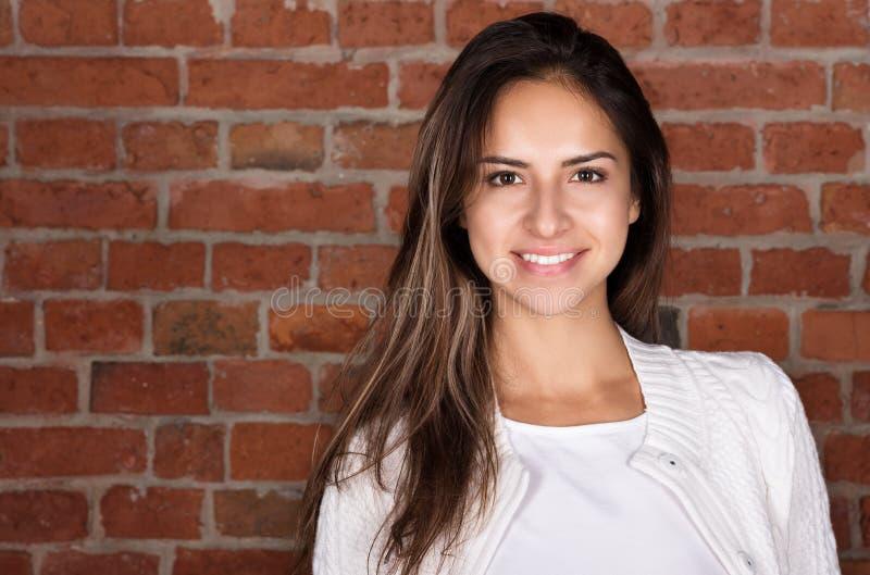 Портрет красивой молодой женщины против кирпичной стены стоковые изображения rf