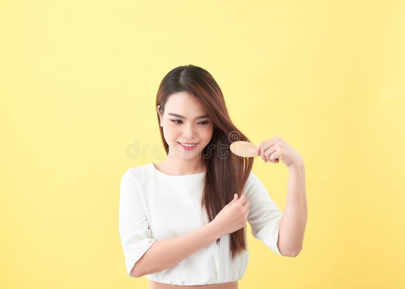 Портрет красивой молодой женщины расчесывая ее волосы и усмехаться стоковое фото rf
