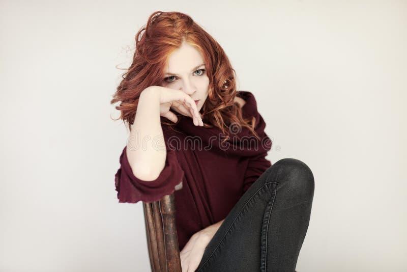 Портрет красивой молодой женщины с длинным красным вьющиеся волосы и совершенные составляют, уютный красный свитер зимы стоковая фотография