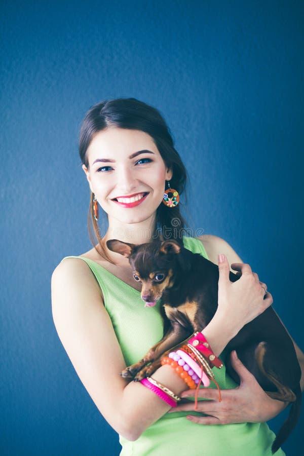 Портрет красивой молодой женщины с собакой на серой предпосылке стоковая фотография rf