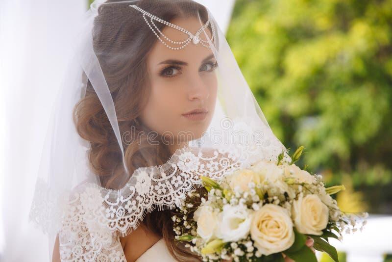 Портрет красивой молодой невесты нося белую вуаль шнурка, потревоженный на ее день свадьбы, держа букет свадьбы стоковые фото