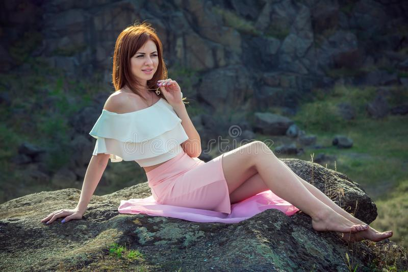 Портрет красивой молодой усмехаясь женщины сидя barefoot на скале стоковые фотографии rf