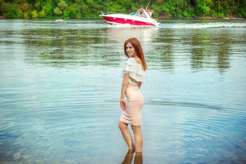Портрет красивой молодой усмехаясь женщины стоя в речной воде стоковые изображения rf