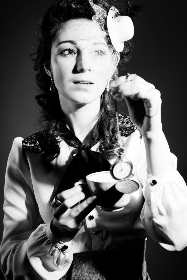 Портрет красивой молодой дамы с чашкой питья и карманным вахтой на светлой предпосылке стоковые фото