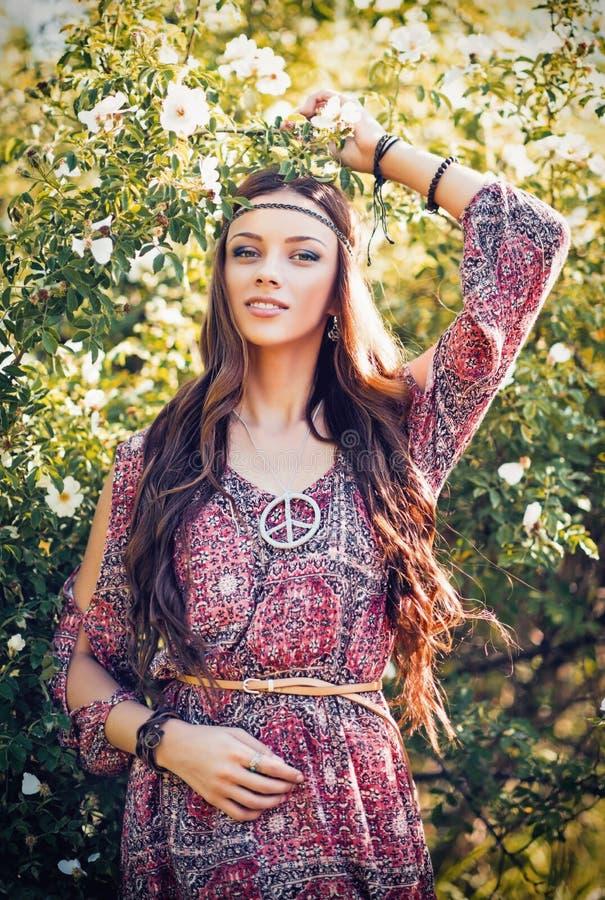 Портрет красивой молодой девушки hippie среди цветков стоковое изображение
