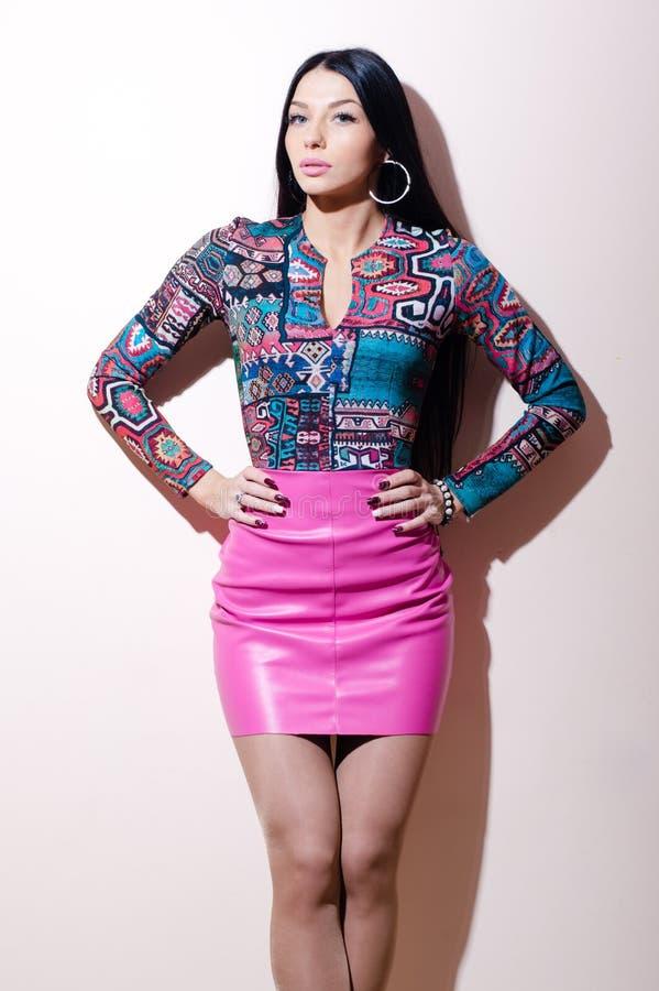Портрет красивой молодой женщины брюнет при голубые глазы стоя в розовом кожаном платье смотря камеру на белизне стоковая фотография
