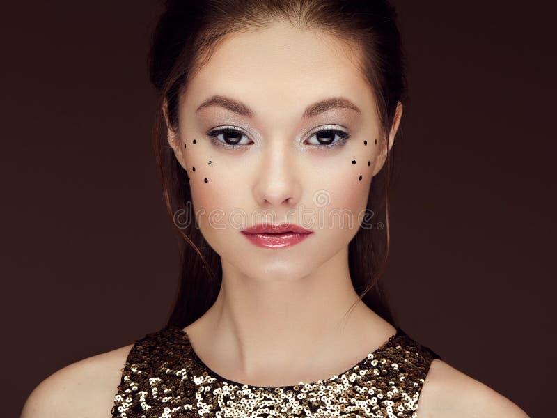 Портрет красивой молодой женщины в сияющем золотом платье стоковые фото