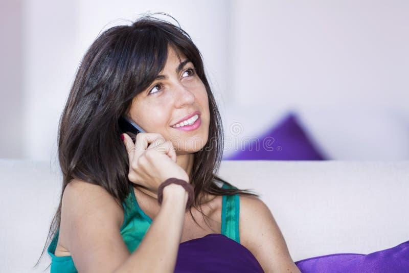 Портрет красивой молодой женщины говоря на телефоне в гостиничном номере стоковая фотография rf
