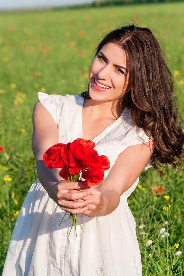 Портрет красивой молодой женщины держа букет маков в поле стоковые изображения rf