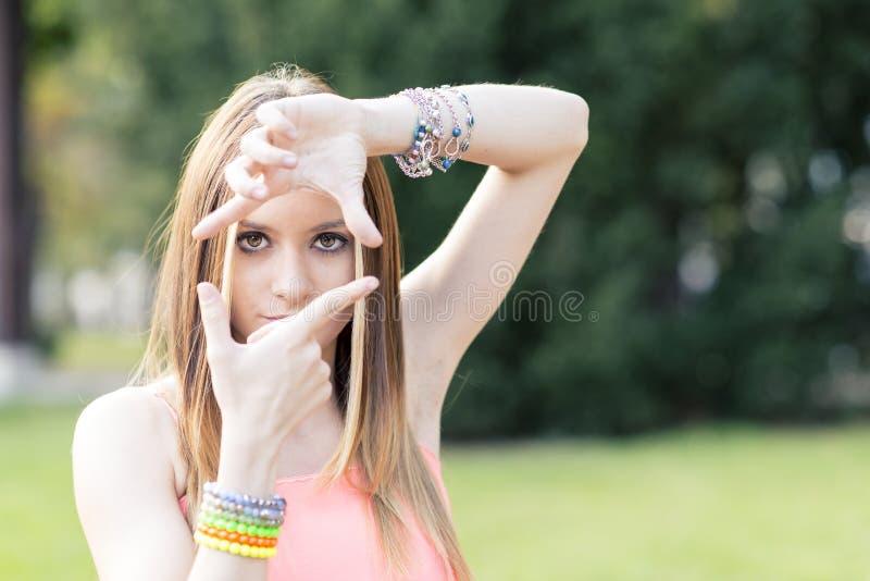 Портрет красивой молодой женщины делая рамку с ее руками стоковое изображение