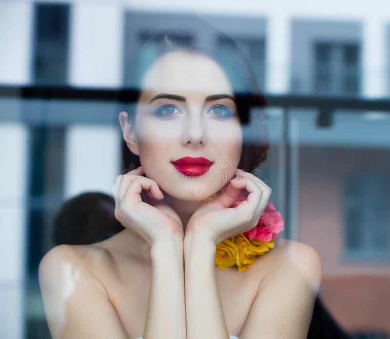 Портрет красивой молодой женщины стоя около окна и l стоковая фотография rf