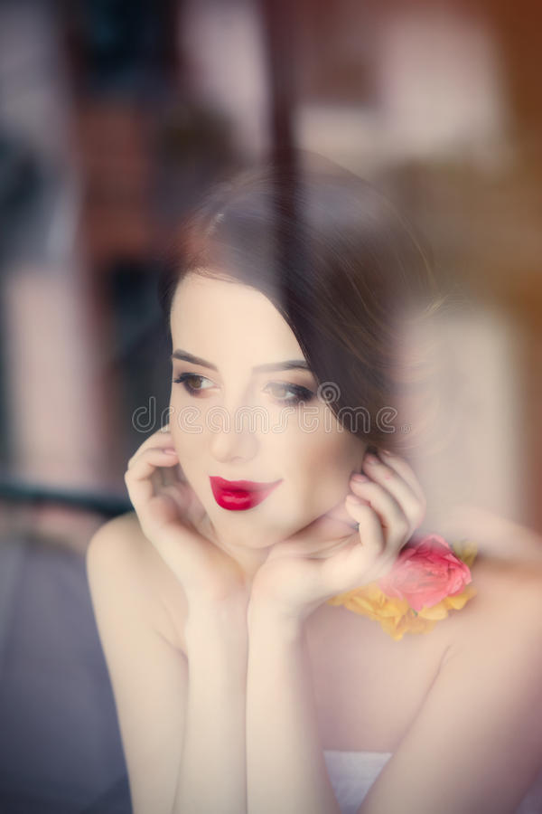 Портрет красивой молодой женщины стоя около окна и l стоковое изображение