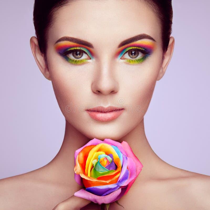 Портрет красивой молодой женщины с радугой поднял стоковое фото