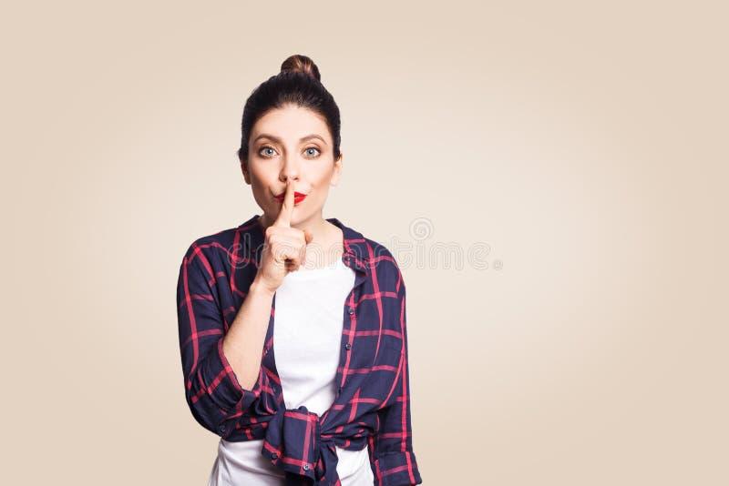 Портрет красивой молодой кавказской женщины при плюшка черных волос держа указательный палец на губах стоковая фотография