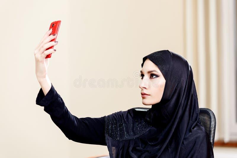 Портрет красивой мусульманской женщины которая делает фото стоковая фотография