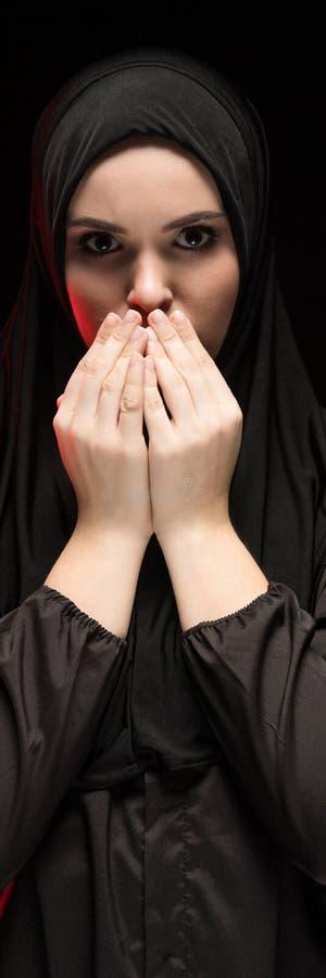 Портрет красивой серьезной молодой мусульманской женщины нося черное hijab с руками приближает к ее стороне как моля концепция да стоковое изображение rf