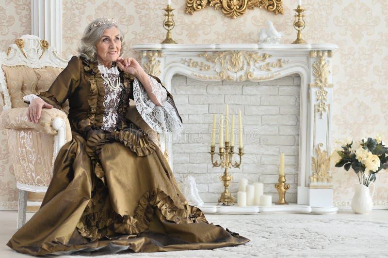Портрет красивой старшей женщины в ферзе платья, представляя внутри помещения стоковые изображения
