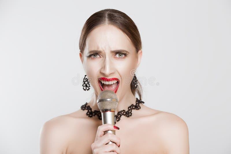 Портрет красивой стильной женщины, громко поющей в микрофон, смотрящей на камеру, на белом фоне стены Лицо человека стоковые изображения rf