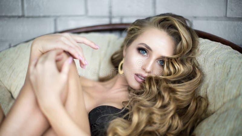 Портрет красивой стильной женщины с вьющиеся волосы ослабляя в кресле стоковое изображение rf